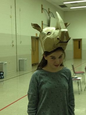 Cast member Maddie Gerig wearing the rhino head in its bare cardboard state.